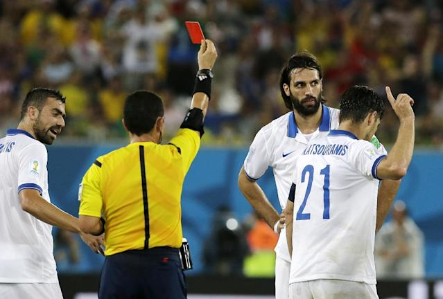 Greece's Kostas Katsouranis (21) gestures at referee Joel Aguilar from El Salvador after being sent off with a red card during the group C World Cup soccer match between Japan and Greece at the Arena das Dunas in Natal, Brazil, Thursday, June 19, 2014. (AP Photo/Shuji Kajiyama)