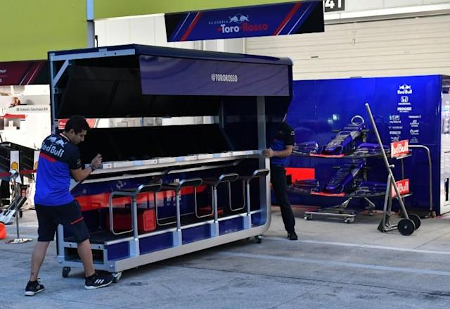 Toro Rosso team mechanics remove a pit wall control desk to prepare for typhoon Hagibis at Suzuka (AFP Photo/TOSHIFUMI KITAMURA)