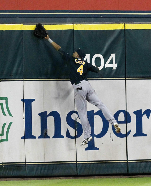 Oakland Athletics' Coco Crisp (4) leaps at the wall but can't make a catch on a home run hit by Houston Astros' Matt Dominguez in the ninth inning of a baseball game on Tuesday, July 23, 2013, in Houston. The Astros won 5-4. (AP Photo/Bob Levey)