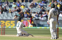 Australia's Matthew Wade, left, kneels on the ground after he was run-out for 33 runs against India on the third day of their cricket test match at the Adelaide Oval in Adelaide, Australia, Saturday, Dec. 19, 2020. (AP Photo/David Mariuz)