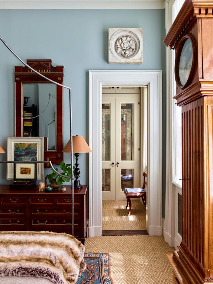 """<div class=""""caption""""> """"I love layers and things that tell a story,"""" says Schafer. """"Anyone who's in this business falls in love with objects to their own peril."""" In the bedroom, which is painted in <a href=""""https://www.farrow-ball.com/en-us"""" rel=""""nofollow noopener"""" target=""""_blank"""" data-ylk=""""slk:Farrow & Ball"""" class=""""link rapid-noclick-resp"""">Farrow & Ball</a>'s Light Blue, an antique carpet found in Maine sits atop sea-grass wall-to-wall carpeting by <a href=""""https://pattersonflynnmartin.com/"""" rel=""""nofollow noopener"""" target=""""_blank"""" data-ylk=""""slk:Patterson Flynn & Martin"""" class=""""link rapid-noclick-resp"""">Patterson Flynn & Martin</a>. The 1940s chest of drawers from <a href=""""https://sutterantiques.com/"""" rel=""""nofollow noopener"""" target=""""_blank"""" data-ylk=""""slk:Sutter Antiques"""" class=""""link rapid-noclick-resp"""">Sutter Antiques</a> is topped with a Russian mirror from <a href=""""http://www.evergreenantiques.com/"""" rel=""""nofollow noopener"""" target=""""_blank"""" data-ylk=""""slk:Evergreen Antiques"""" class=""""link rapid-noclick-resp"""">Evergreen Antiques</a> and a contemporary pastel landscape sketch from <a href=""""http://www.charlesplante.com/"""" rel=""""nofollow noopener"""" target=""""_blank"""" data-ylk=""""slk:Charles Plante Fine Arts"""" class=""""link rapid-noclick-resp"""">Charles Plante Fine Arts</a>. A plaster ceiling medallion found at the Pier Antiques Show hangs above a doorframe leading to the dressing area. </div>"""