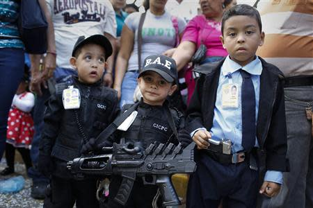 Children dressed as police officers attend a parade during the Carnival festival in Caracas March 4, 2014. REUTERS/Carlos Garcia Rawlins
