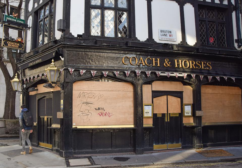 LONDON, UNITED KINGDOM - 2021/02/18: A man walks past the closed Coach & Horses pub in Central London. Coronavirus cases are falling across the UK, as the government prepares to present its plan for easing the lockdown restrictions. (Photo by Vuk Valcic/SOPA Images/LightRocket via Getty Images)