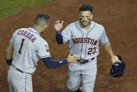 Houston Astros' Jose Altuve is congratulated by Carlos Correa after scoring during the fifth inning of Game 3 of the baseball World Series against the Washington Nationals Friday, Oct. 25, 2019, in Washington. (AP Photo/Pablo Martinez Monsivais)