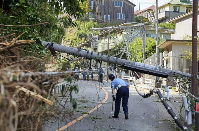 A police officer inspects a fallen utility pole downed by winds caused by Typhoon Faxai in Kamakura, Kanagawa prefecture. Rugby World Cup organisers say they have learnt and adjusted their contingency plans in case of further bad weather