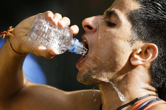 Baljinder Singh of India drinks water while competing in the men's 20-kilometer race walk, at the 2012 Summer Olympics, Saturday, Aug. 4, 2012, in London. (AP Photo/Markus Schreiber)