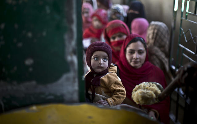 <p>A child is held by his mother as they wait to receive rice during a donated food distribution on the occasion of Prophet Mohammad's birthday, at a shrine in Islamabad, Pakistan, Jan. 14, 2014. (Photo: Muhammed Muheisen/AP) </p>