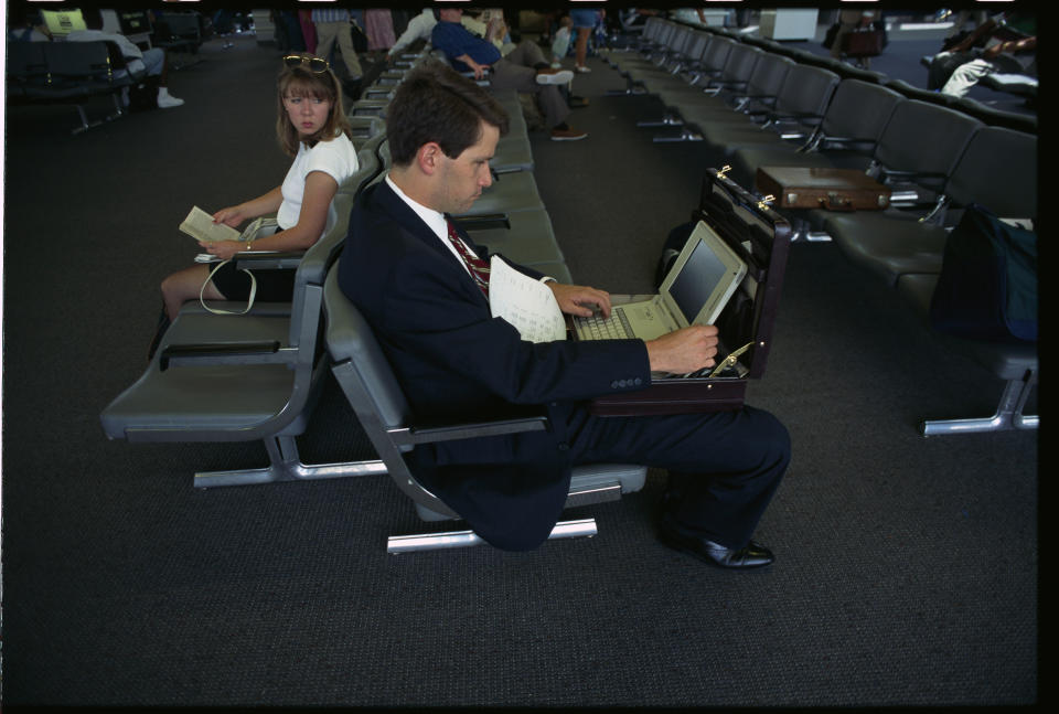 A businessman waiting at the US Air terminal in La Guardia Airport works on his laptop computer. (Photo by mark peterson/Corbis via Getty Images)