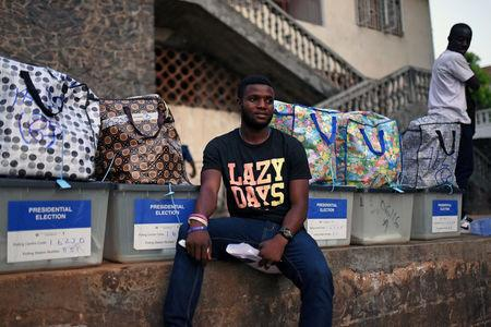 A man sits next to ballot boxes to be collected from a polling station during a presidential run-off in Freetown, Sierra Leone March 31, 2018. REUTERS/Olivia Acland