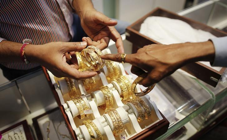 An employee shows gold bangles to a customer at jewellery showroom on the occasion of Dhanteras, a Hindu festival associated with Lakshmi, the goddess of wealth, at a market in Mumbai
