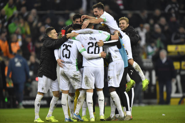 Moenchengladbach's Ramy Bensebaini, left,, celebrates with team mates, at the end of the German Bundesliga soccer match between Borussia Moenchengladbach and Bayern Munich at the Borussia Park in Moenchengladbach, Germany, Saturday, Dec. 7, 2019. (AP Photo/Martin Meissner)