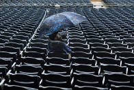 A baseball fan sits under an umbrella in the left field stands at PNC Park during a rain storm that forced a delay during the eighth inning of a baseball game between the Pittsburgh Pirates and the Los Angeles Dodgers in Pittsburgh, Thursday, June 10, 2021. (AP Photo/Gene J. Puskar)