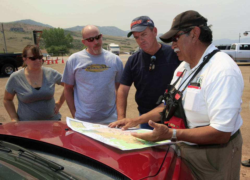 Bernie Pineda, right, of the U.S. Forest Service, uses a map to show the progress of a wildfire to Jeannine Larsen, far left, and Dan Erickson, who own a property in the Glacier View subdivision, and James Pearl, third from left, near Livermore, Colo., on Saturday, June 23, 2012. The couple said that their home is in danger of burning and Pearl, who built a home in the Deer Meadows subdivision, said his was destroyed already. Authorities sent out 992 evacuation notices Friday due to the wildfire burning on more than 100 square miles in northern Colorado as winds pick up. (AP Photo/David Zalubowski)