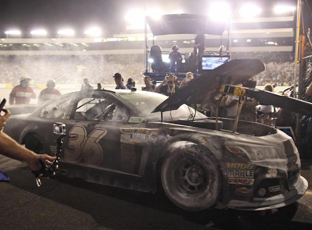 Reed Sorenson's car is towed to the garage area after a fire during the NASCAR Sprint Cup auto race at Richmond International Raceway in Richmond, Va., Saturday, April 26, 2014. (AP Photo/Zach Gibson)