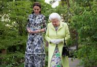 """<p>Kate Middleton and Queen Elizabeth II are pictured here walking around the """"Back to Nature"""" garden at the May 2019 RHS Chelsea Flower Show. The Queen donned bright green and purple hues. Kate's navy dress featured small yellow accents. </p>"""