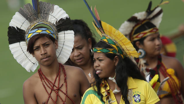 Brazilian Indians watch Germany's national soccer team during a training session near Porto Seguro, Brazil, Monday, June 9, 2014. Germany will play in group G of Brazil's 2014 soccer World Cup. (AP Photo/Matthias Schrader)