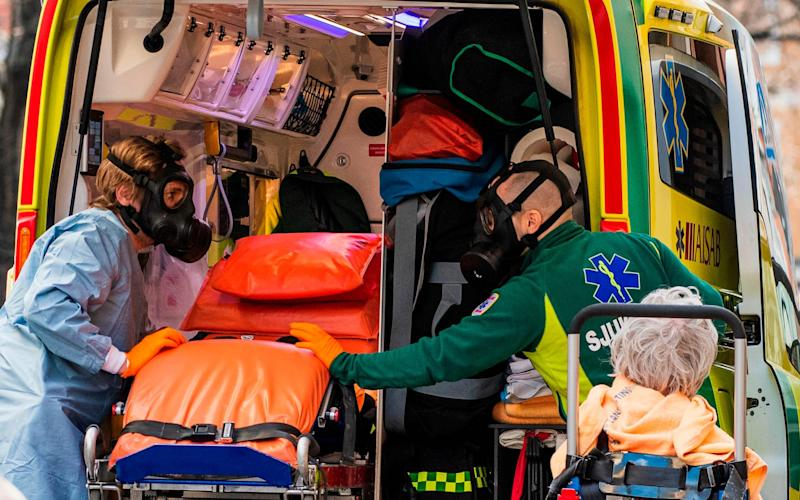 Paramedics with protective gas masks help to transport a patient - AFP