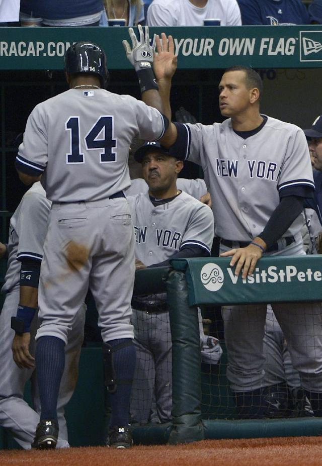 New York Yankees' Curtis Granderson (14) is congratulated by Alex Rodriguez after Granderson hit a sacrifice fly to score the game-winning run in the 11th inning of a baseball game against the Tampa Bay Rays in St. Petersburg, Fla., Sunday, Aug. 25, 2013. The Yankees won 3-2. (AP Photo/Phelan M. Ebenhack)