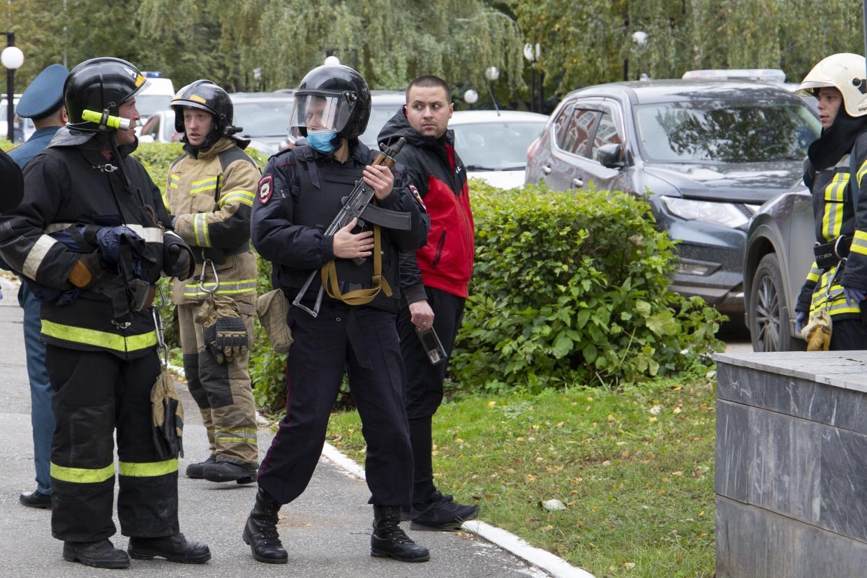 An armed police officer and firefighters gather at the Perm State University in Perm, about 700 miles east of Moscow, Russia, Monday, Sept. 20, 2021.