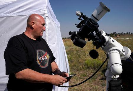 Rick Roty works with his telescope in a designated eclipse viewing area in a campground near Guernsey, Wyoming, U.S., August 20, 2017. REUTERS/Rick Wilking