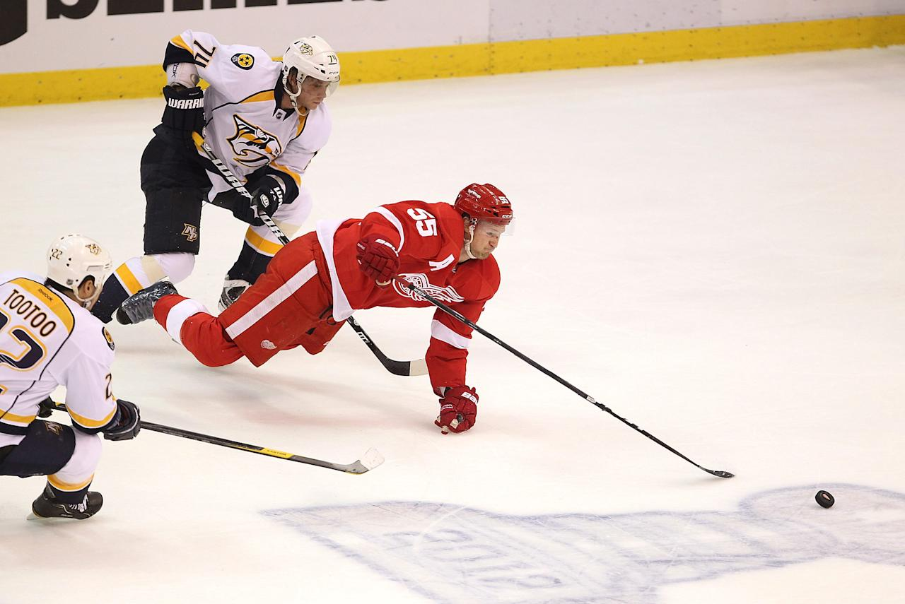 DETROIT, MI - APRIL 15: Niklas Kronwall #55 of the Detroit Red Wings dives for the puck in front of Sergei Kostitsyn #74 of the Nashville Predators during Game Three of the Western Conference Quarterfinals during the 2012 NHL Stanley Cup Playoffs at Joe Louis Arena on April 15, 2012 in Detroit, Michigan. (Photo by Gregory Shamus/Getty Images)