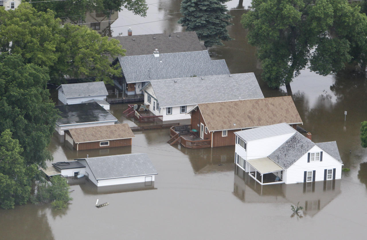 In this aerial photo the flood waters of the Souris River flow through a neighborhood Friday, June 24, 2011 in Minot, N.D., The Souris River set a record for flooding, rising so quickly that it could be seen climbing up the side of homes in the North Dakota city. (AP Photo/Charles Rex Arbogast)