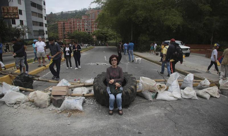 A woman rests on a tyre at a roadblock set up by residents outside her home in El Hatillo, near Caracas, on Tuesday.