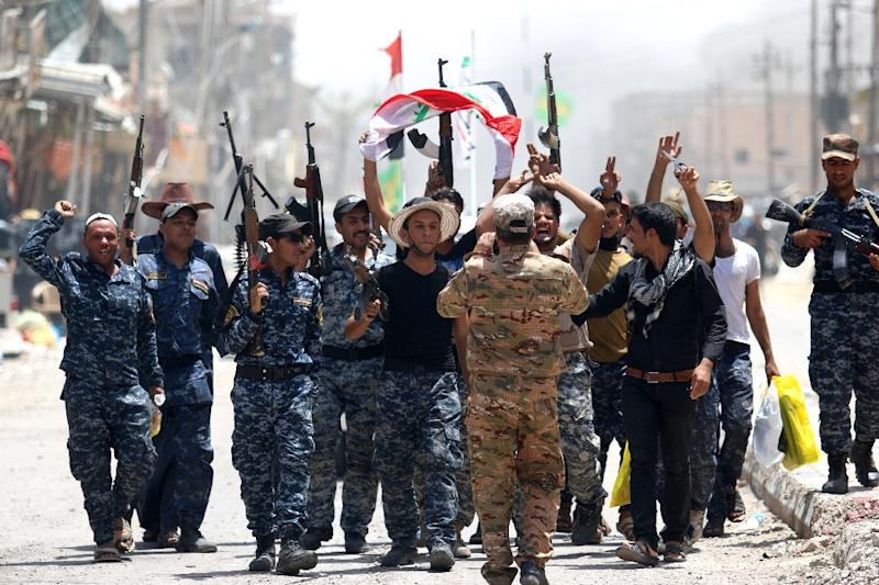 Members of Iraqi police forces celebrate on a street on June 27, 2016 in western Fallujah, 50 kilometres (30 miles) from the Iraqi capital Baghdad, after Iraqi forces retook the embattled city from the Islamic State group (AFP Photo/Haidar Mohammed Ali)
