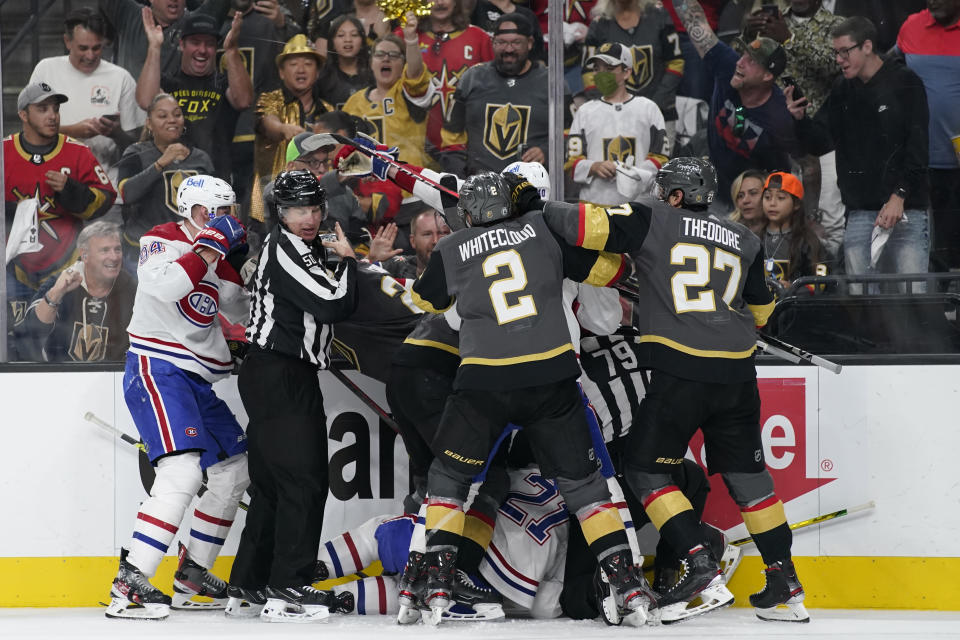 Referees attempt to break up a shoving match during the second period in Game 2 of an NHL hockey Stanley Cup semifinal playoff series between the Vegas Golden Knights and the Montreal Canadiens, Wednesday, June 16, 2021, in Las Vegas. (AP Photo/John Locher)