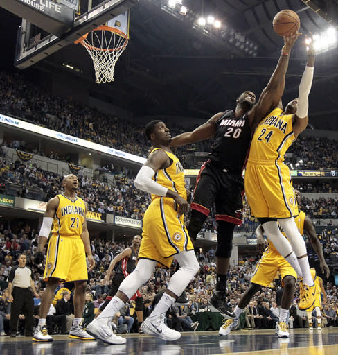 Miami Heat center Greg Oden, center, battles for a rebound with the Indiana Pacers Paul George, right, and Roy Hibbert during the first half of an NBA basketball game in Indianapolis, Wednesday, March 26, 2014. (AP Photo/AJ Mast)
