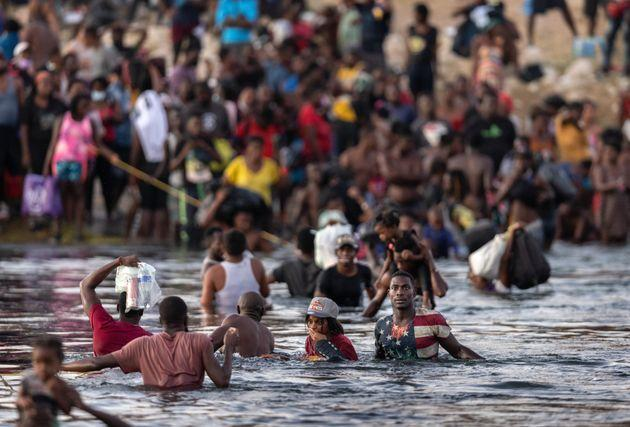 CIUDAD ACUNA, TEXAS - SEPTEMBER 19: Immigrants, mostly from Haiti gather on the bank of the Rio Grande on September 19, 2021 in Ciudad Acuna, Mexico, across the border from Del Rio, Texas. As U.S. immigration authorities began deporting immigrants back to Haiti from Del Rio, thousands more waited in a camp under an international bridge in Del Rio and others crossed the river back into Mexico. (Photo by John Moore/Getty Images) (Photo: John Moore via Getty Images)