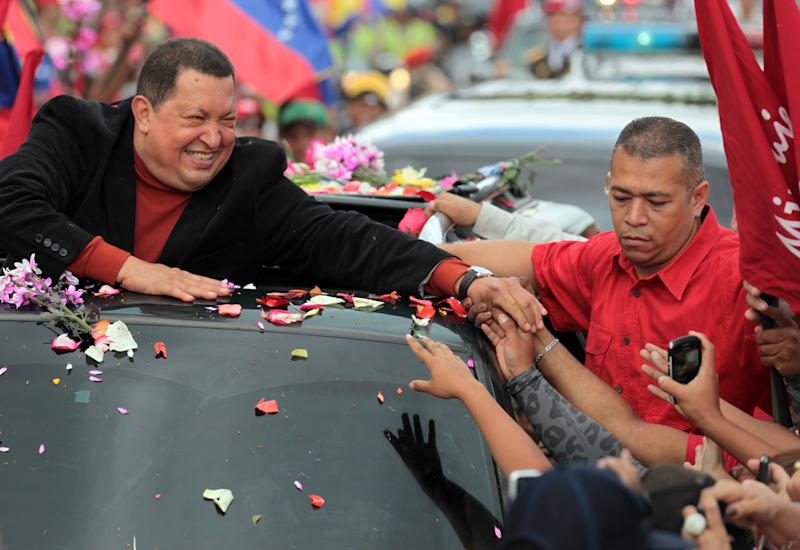 Venezuela's President Hugo Chavez, left, greets supporters during his caravan from Miraflores presidential palace to the airport in Caracas, Venezuela, Friday Feb. 24, 2012. Chavez bid an emotional goodbye to soldiers and supporters and waved to crowded streets in Caracas on his way to Cuba for urgent surgery to remove a tumor he says is probably malignant. (AP Photo/Fernando Llano)