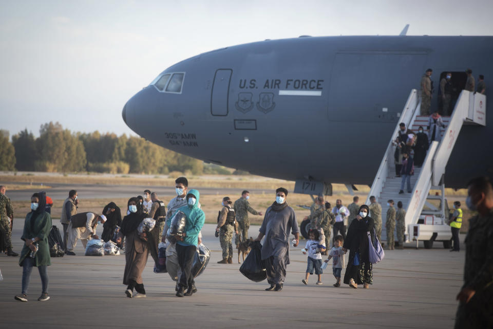 Evacuees from Afghanistan disembark from a U.S. airforce plane at the Naval Station in Rota, southern Spain, Tuesday Aug 31, 2021. The United States completed its withdrawal from Afghanistan late Monday, ending America's longest war. (AP Photo/ Marcos Moreno)