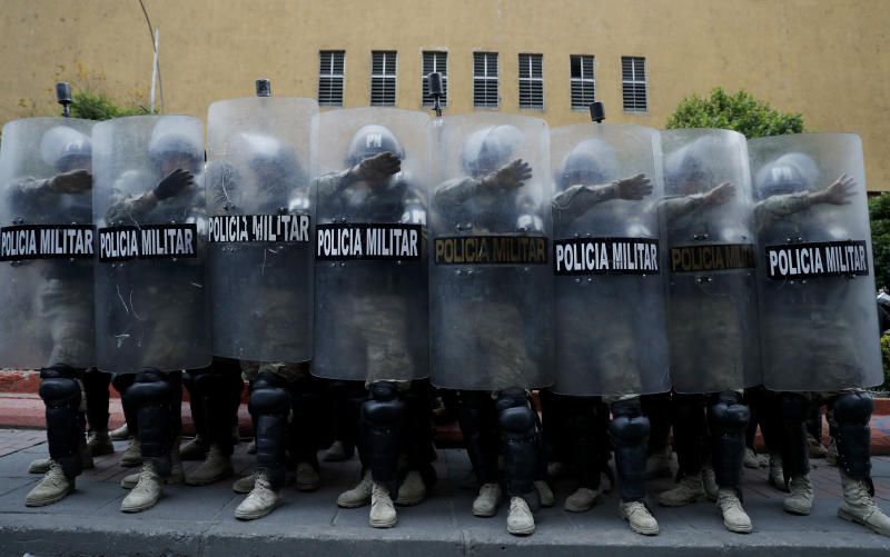 Military Police take cover behind their shields during a march of supporters of former President Evo Morales in La Paz, Bolivia, Thursday, Nov. 14, 2019. Morales resigned and flew to Mexico under military pressure following massive nationwide protests over alleged fraud in an election last month in which he claimed to have won a fourth term in office. (AP Photo/Natacha Pisarenko)