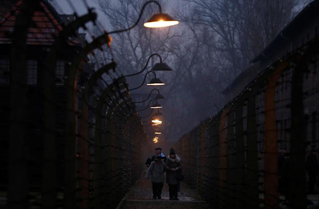 <p>Survivors and guests walk inside the barbed wire fences at the former Nazi German concentration and extermination camp Auschwitz, during the ceremonies marking the 73rd anniversary of the liberation of the camp and International Holocaust Victims Remembrance Day, in Oswiecim, Poland, Jan. 27, 2018. (Photo: Kacper Pempel/Reuters) </p>