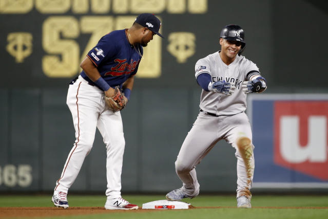 New York Yankees' Gleyber Torres, right, celebrates in front of Minnesota Twins second baseman Luis Arraez, left, after hitting a double in the seventh inning in Game 3 of a baseball American League Division Series, Monday, Oct. 7, 2019, in Minneapolis. (AP Photo/Bruce Kluckhohn)