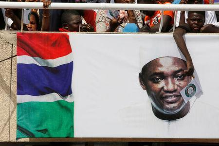 A supporter of Gambia President Adama Barrow wave ECOWAS flag during his swearing-in ceremony and the Gambia's Independence day at Independence Stadium, in Bakau, Gambia February 18, 2017. REUTERS/Thierry Gouegnon