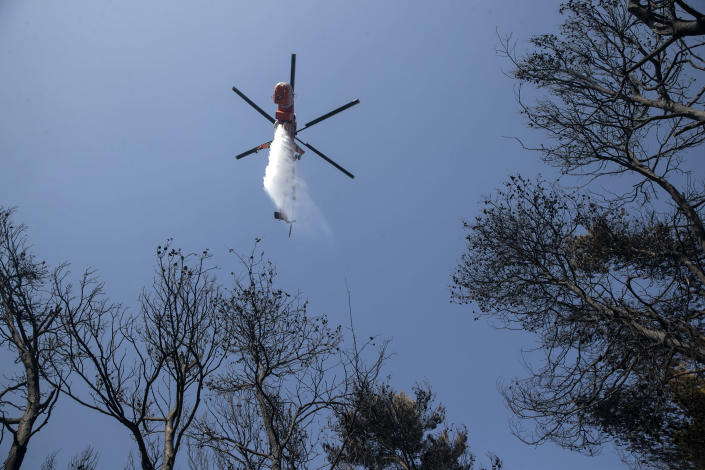 A firefighting helicopter drops water during a forest fire at Dionysos northern suburb of Athens, on Tuesday, July 27, 2021. Greek authorities have evacuated several areas north of Athens as a wildfire swept through a hillside forest and threatened homes despite a large operation mounted by firefighters. (AP Photo/Yorgos Karahalis)