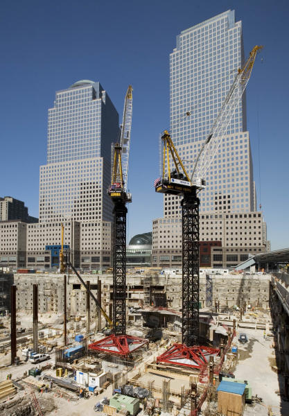 """FILE - In this May 30, 2007 file photo, construction cranes work over the """"Freedom Tower"""" construction site in New York. The World Trade Center, destroyed in the attacks of Sept. 11, 2001, will be anchored by One World Trade Center, as well as three additional office towers, a memorial and a transportation hub. The World Financial Center buildings in the background are occupied by Merrill Lynch, left, and American Express. (AP Photo/Mark Lennihan, File)"""