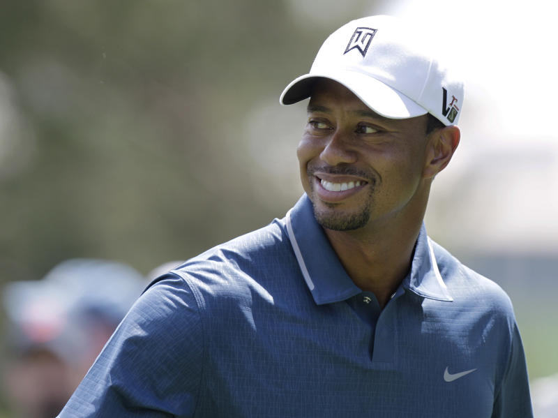 Tiger Woods smiles at his caddie on the 15th hole during the pro-am of the Memorial golf tournament Wednesday, May 29, 2013, in Dublin, Ohio. (AP Photo/Jay LaPrete)