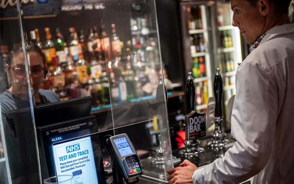 A screen at the till asks customers to register their details for the NHS Test and Trace scheme at a pub in London - Chris J Ratcliffe/Getty Images Europe