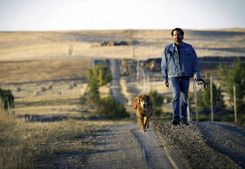 In this Oct. 2011 photo provided by Explore.org, philanthropist Charlie Annenberg, with his golden retriever, Lucky, take a walk during a visit with the medicine men and people of the Lakota Nation in Pine Ridge, S.D. For 16 years, Lucky has been his sidekick, soul mate and inspiration. In 2010, Annenberg started Dog Bless You, a journal of their travels as told by Lucky but written by Annenberg. (AP Photo/Explore.org)