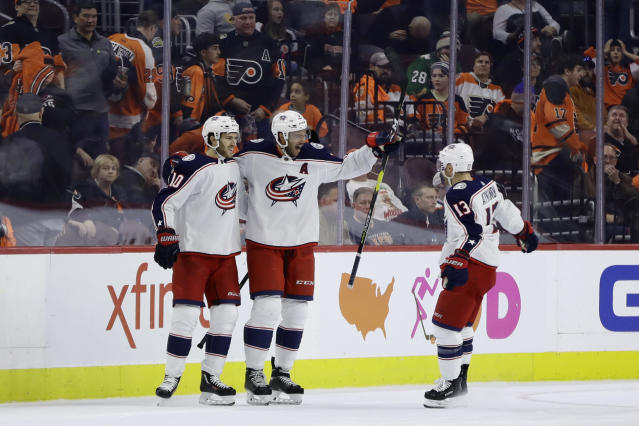Columbus Blue Jackets' Seth Jones, center, celebrates with Cam Atkinson, right, and Alexander Wennberg after scoring in overtime of the team's NHL hockey game against the Philadelphia Flyers, Thursday, Dec. 6, 2018, in Philadelphia. Columbus won 4-3. (AP Photo/Matt Slocum)