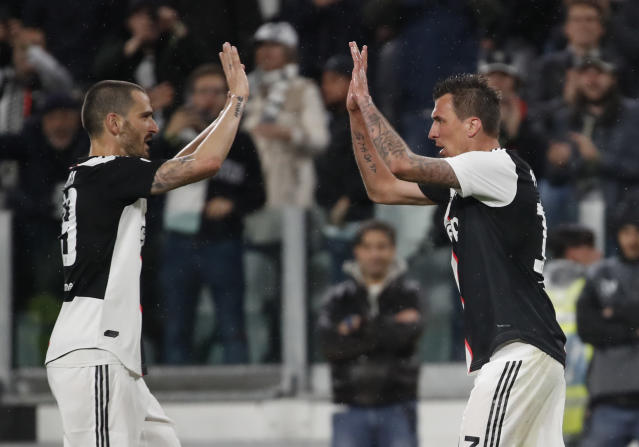 Juventus' Mario Mandzukic, right, celebrates with his teammate Juventus' Leonardo Bonucci after scoring the opening goal during the Serie A soccer match between Juventus and Atalanta at the Allianz stadium, in Turin, Italy, Sunday, May 19, 2019. (AP Photo/Antonio Calanni)