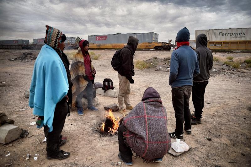 Honduran migrants warm themselves next to a campfire near train tracks in Sonora state, Mexico close to the border with the US, on January 13, 2017 (AFP Photo/ALFREDO ESTRELLA)