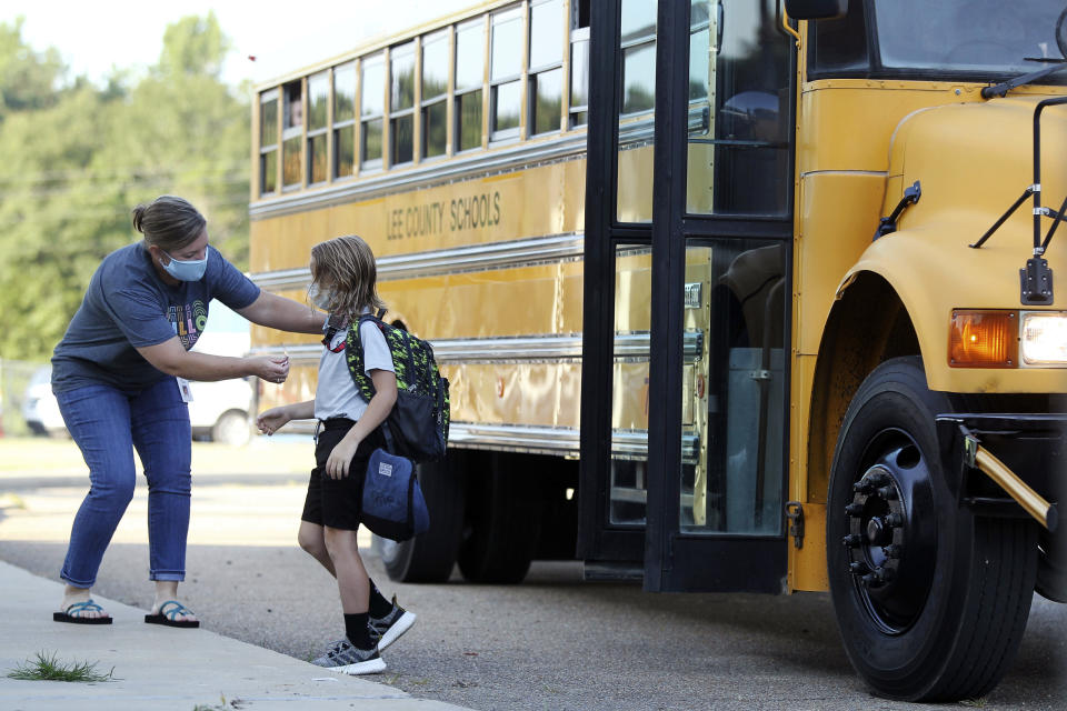 FILE - In this Aug. 6, 2020, file photo, Audrey Wylie, a speech pathologist, at Saltillo Primary School, puts a bus number sticker on Cruz Antle, a first grader, as he gets off the bus for his first day back to school in Saltillo, Miss. As schools reopen around the country, their ability to quickly identify and contain coronavirus outbreaks before they get out of hand is about to be put to the test. (Adam Robison/The Northeast Mississippi Daily Journal via AP, File)