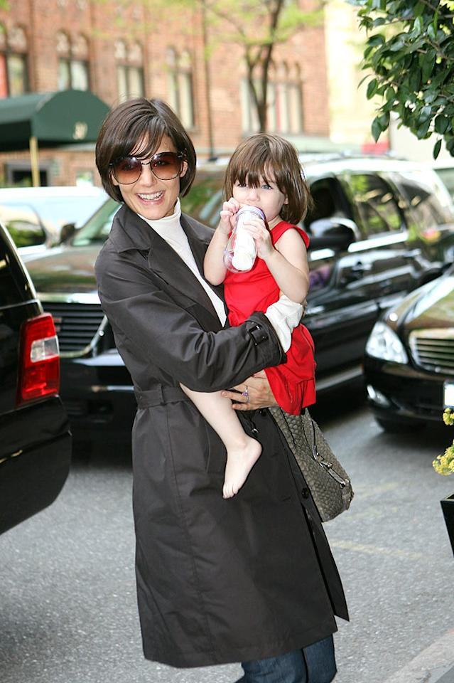 """Suri Cruise makes a fashion statement in a bold red dress and bare feet. The toddler completes her look with a baby bottle. <a href=""""http://www.infdaily.com"""" target=""""new"""">INFDaily.com</a> - May 5, 2008"""