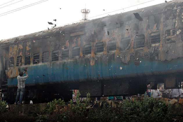 A videojournalist (L) records footage of a gutted train carriage, which caught fire from an electrical short circuit killing at least 32, in Nellore on July 30, 2012. At least 32 people were killed July 30 when a fire ripped through a coach on an express train as it carried sleeping passengers to the southern Indian city of Chennai, officials said. AFP PHOTO/STR
