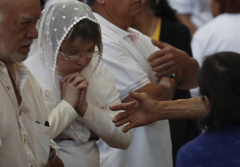 A man stretches out his hand to a woman who rejects the handshake during a Mass at the Metropolitan Cathedral in Mexico City, Sunday, March 1, 2020. Church leaders had requested for the faithful to abstain from shaking hands or embracing during the day's services to help slow down the spread of the new coronavirus COVID-19. (AP Photo/Marco Ugarte)