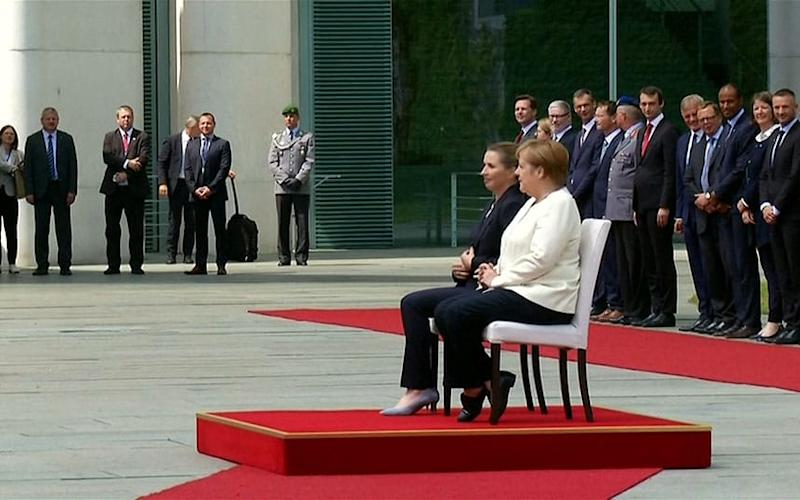 Angela Merkel sits during national anthem after bouts of shaking